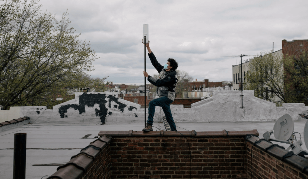 Daniel Heredia working this spring to bring inexpensive Wi-Fi to a building in Brownsville, Brooklyn.Credit...Jose A. Alvarado Jr. for The New York Times